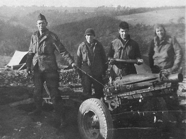 Sartain's driver, Louis Sosa (second from left), and a glider artillery gun crew pose by a 75mm pack howitzer, Holland, October 1944. The gun was relatively light (1,439 pounds), easily transportable, and had a maximum range of approximately five miles.