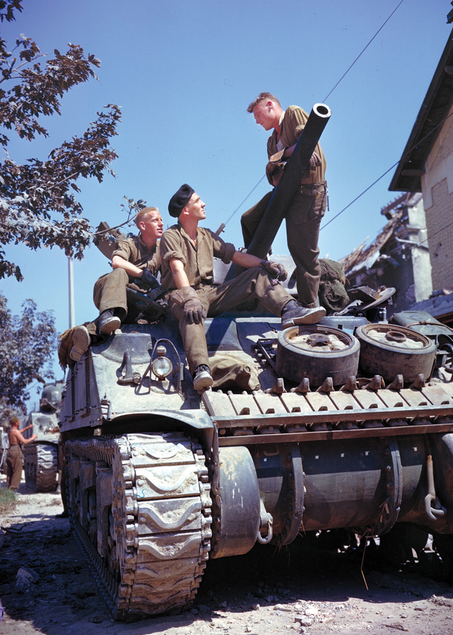 The crew of a Canadian Sherman tank rests in the village of Vaucelles, France, during the Normandy campaign in the summer of 1944. The American-designed Sherman was also built under license in Canada.
