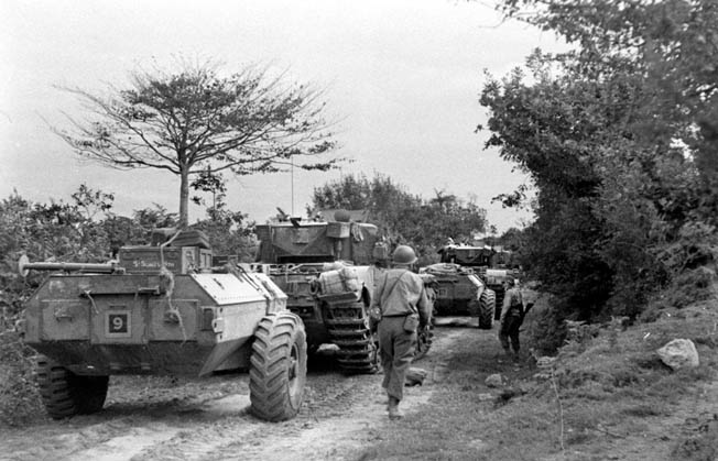 British flamethrower tanks, Churchills that were dubbed 'Crocodiles,' move forward toward Geilenkirchen along with American infantrymen. These tanks proved to be of great value in reducing enemy-occupied machine gun positions and bunkers during the fight to reduce the salient.