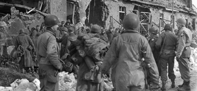 German prisoners of the 164th and 183rd Infantry Regiments are herded into the forester's lodge near the Wahlerscheid Crossroads on February 2, 1945. These U.S. troops from the 9th Infantry Regiment, 2nd Division have taken charge of the German captives and will soon herd them to transport toward prison camps.