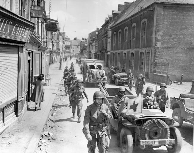 Americans move through Carentan on June 14 after the town was taken. Capture of the key crossroads not only linked up American forces at Utah and Omaha Beaches, but also led the way for advances on Cherbourg and St. Lo.