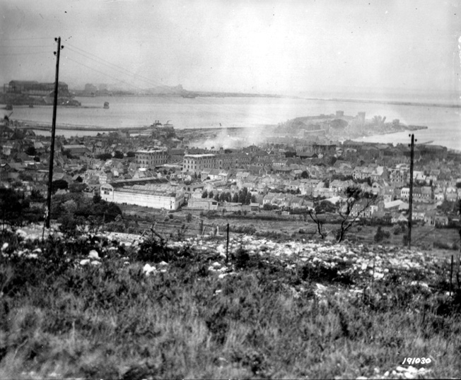 This view of a smoking Cherbourg, with the vital harbor in the distance, was taken after the 79th Division took Fort du Roule on June 26.