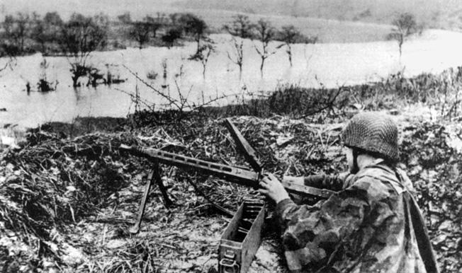 A veteran German grenadier mans an MG42 machine gun after a fierce storm flooded the Cotentin Peninsula in mid-June.