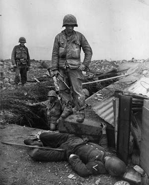 Soldiers from the hard-fighting U.S. 79th Division check for German survivors after capturing Fort du Roule at Cherbourg on June 26, 1944.
