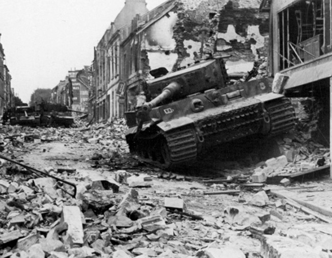 On June 30, 1944, two weeks after Wittmann's astounding feat of gunnery, his Tiger I tank lies disabled and abandoned in Villers-Bocage following an Allied bombing attack.