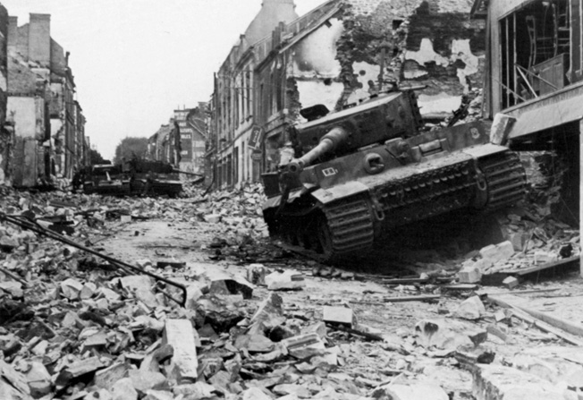 On June 30, 1944, two weeks after Wittmann's astounding feat of gunnery, his Tiger I tank lies dis- abled and abandoned in Villers-Bocage following an Allied bombing attack.