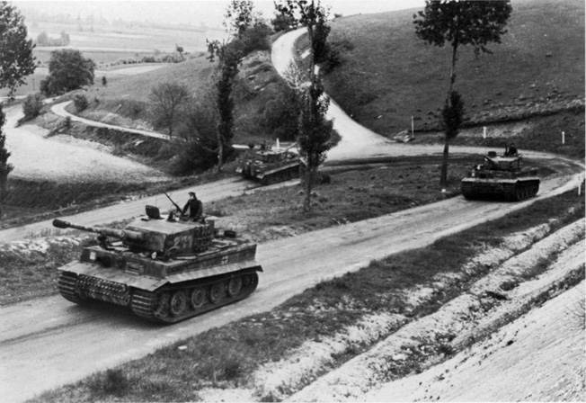 The Tigers of Obersturmführer Michael Wittmann's 2nd Company of the 101st SS Heavy Tank Battalion round a curve on their way to the front.