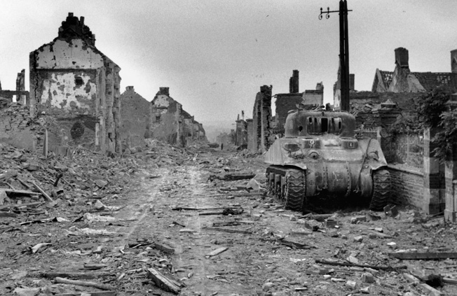 The British recaptured what was left of Villers- Bocage on August 5, 1944. This view of a knocked- out Sherman tank and ruined buildings reveals the extent of the damage that two months of fierce combat had wrought.