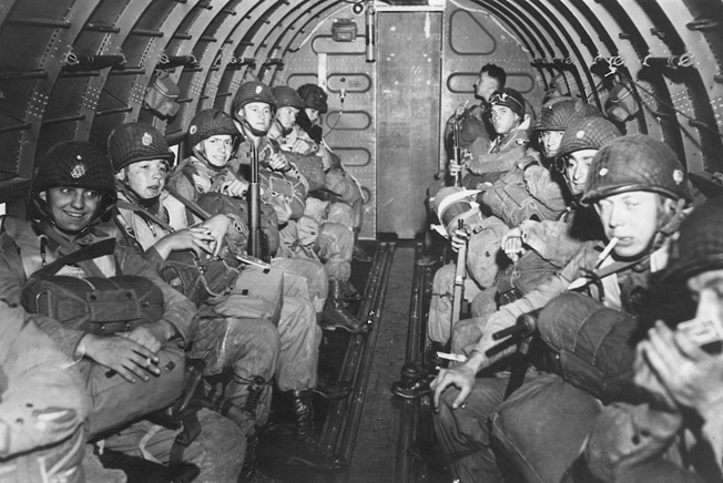 Laden with combat gear, American airborne troops await orders to stand up, hook up, and jump.