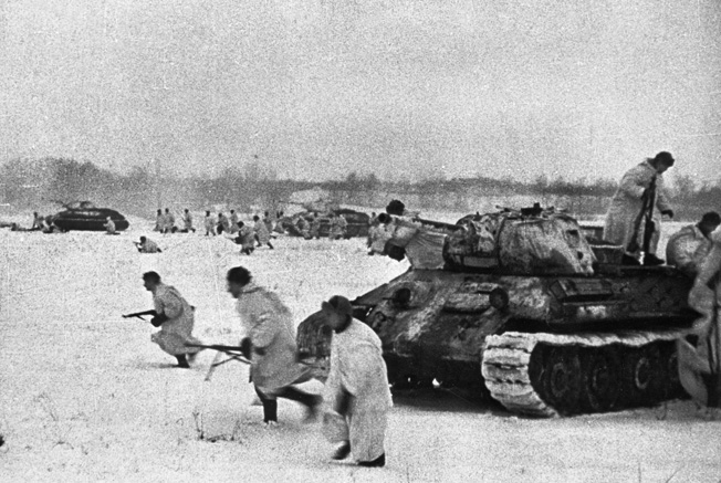 Red Army infantry leap from their accompanying T-34 tanks to attack German positions in a village.