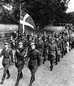 Marching behind the Danish colors, volunteers in the 1st Battalion of Frikorps Danmark march to their barracks upon arrival in Germany, July 1941. Before long they would be fighting in the snows of Russia.
