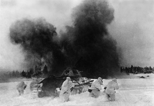 White-clad Red Army infantry, accompanied by a T-34 tank, charge toward German-held positions during the Soviet winter counteroffensive in the Demyansk and Kholm pockets.