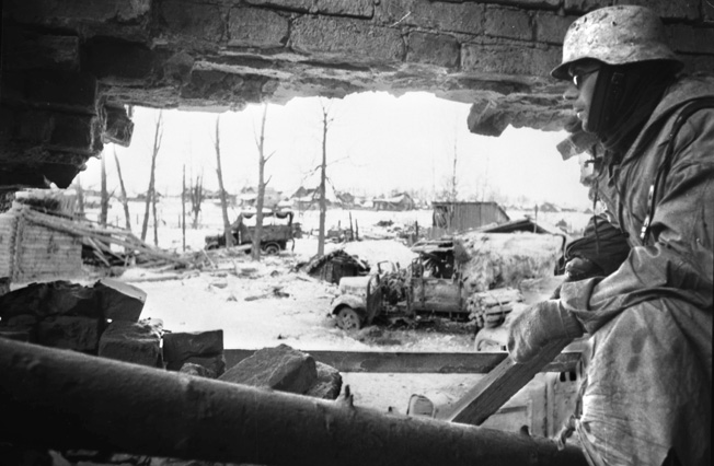 Bleak future: A German soldier tries to stay warm in the shelter of a demolished building while keeping a eye out for Soviet attacks in the Demyansk Pocket.