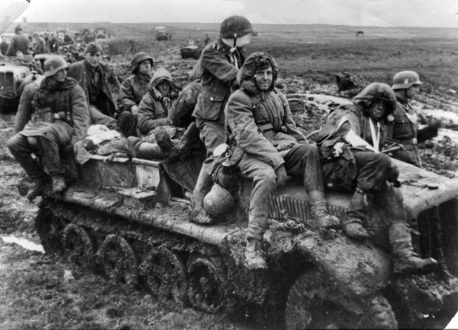 Men of Max Simon's 3rd SS Panzer Division Totenkopf, many of whom are wounded, slog through Russian mud to rear positions, spring 1942.