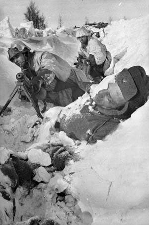 Ignoring a dead Soviet soldier (foreground), two German soldiers man their frigid MG 34 machine-gun position at Demyansk.