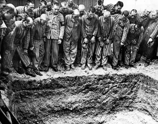 Prisoners at German-run concentration camps were segregated by nationality. Here, a group of Danes at the Dachau camp, where Jorgensen was interned, stand around one of the burial pits they were forced to dig for their deceased countrymen.
