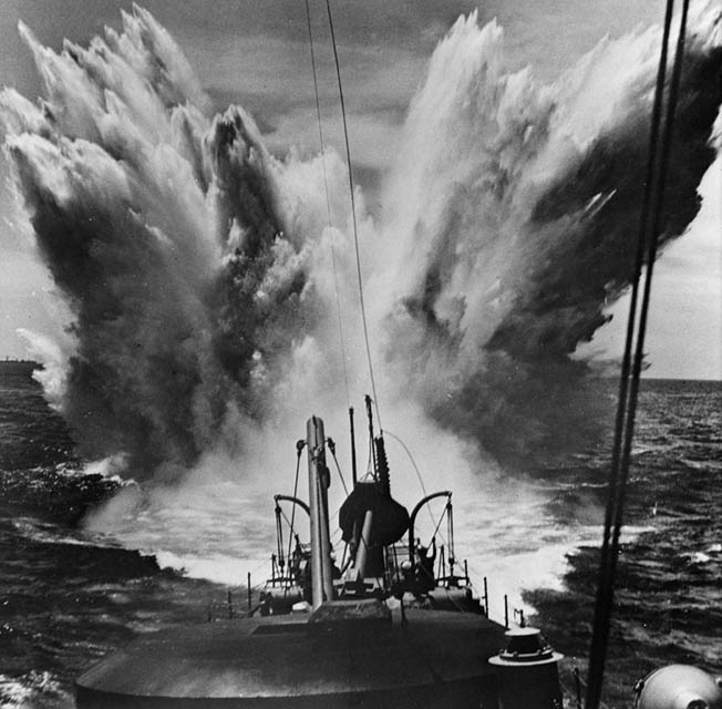 A depth charge sends a plume of water skyward as it detonates off the fantail of a destroyer in the Atlantic Ocean.