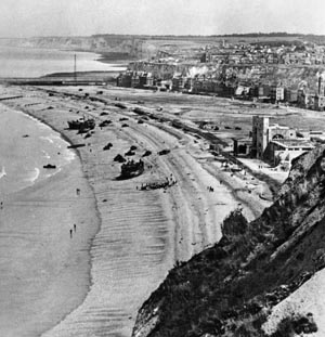 "Knocked-out British and Canadian vehicles litter the ""White"" and ""Red"" landing beaches in this photo taken the day after the raid from the Western Headland. The large building at right is the Dieppe casino, with the town in the background."