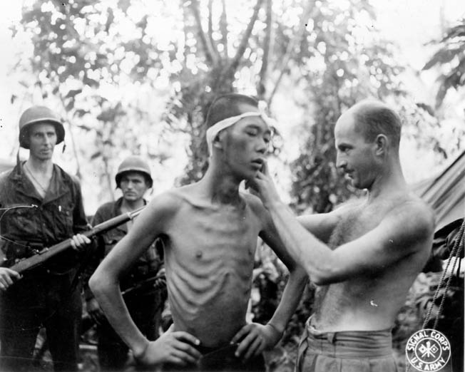 An emaciated Japanese prisoner, one of the lucky Japanese soldiers captured alive in the campaign that culminated with the battle at the Driniumor River, is examined by a medical officer of the 32nd Infantry Division.