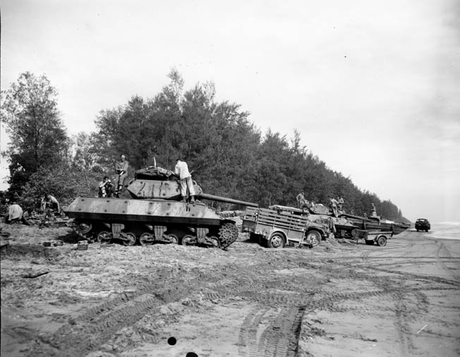 An American tank destroyer and other vehicles attached to the 32nd Infantry Division are readied for an advance against Japanese positions.