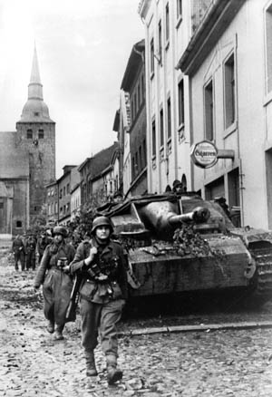 German panzergrenadiers accompanied by a Sturmgeschutz IV assault gun mounting a 75mm main weapon advance through the rubble strewn streets of the city of Aachen.