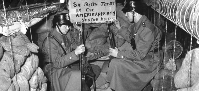 """Berlin, Germany: April 24, 1956. Discovery of an escape and spy tunnel between the Rudow in the Neukoelln district of West Berlin and Alt-Glienicke (Treptow district) in East Berlin.Two armed police guard the tunnel after its discovery. """"Sign You now enter into the American sector"""". © akg-images / Gert Schütz / The Image Works       NOTE: The copyright notice must include """"The Image Works"""" DO NOT SHORTEN THE NAME OF THE COMPANY"""