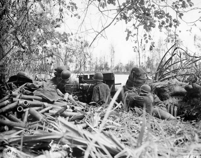 Expended shell casings pile up as American soldiers use a 37mm antitank gun against enemy troops across a river near Buna Mission.