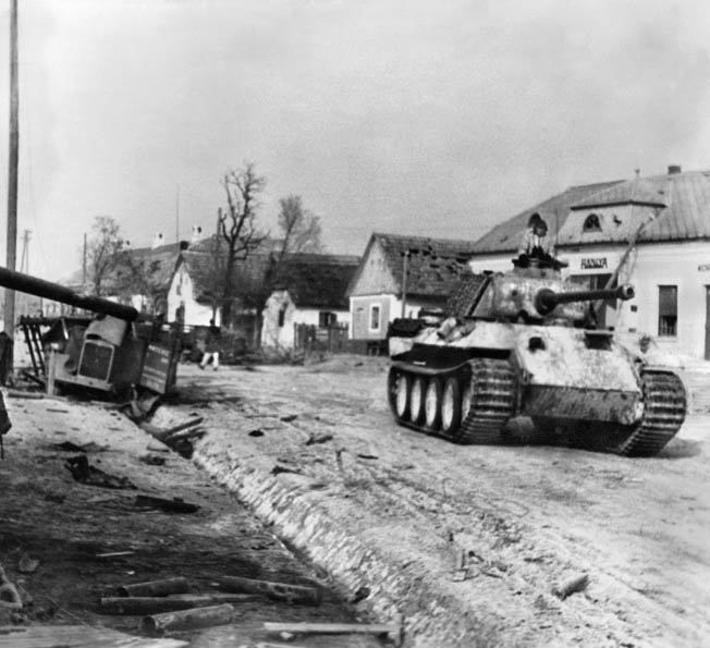 A German Panther in winter camouflage rumbles through a village during Operation Konrad in January 1945. Although badly mauled during the failed offensive to save Budapest from advancing Soviet forces, the IV Panzer Corps was sent into action again in Operation Spring Awakening.