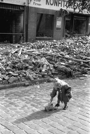 A lucky German girl with a warm coat and a rare toy truck plays in front of a pile of rubble in her bombed-out city.