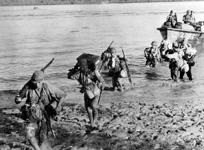 Armed to the teeth and carrying extra ammunition, Japanese soldiers come ashore on the Bataan Peninsula. The Japanese attempted to quicken their pace of conquest via amphibious landings; however, these offensive moves met with fierce resistance.