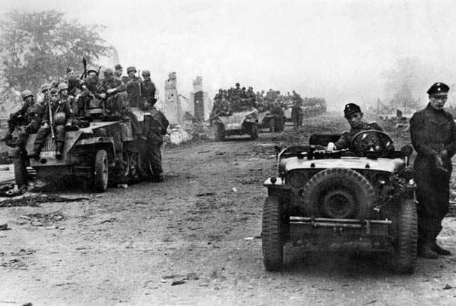 A German soldier drives a captured American jeep while several Sd.Kfz. 250/1 light armored cars (left) are piled with infantry on the Western Front in Holland. Initially caught off guard, the Germans fought back fiercely.