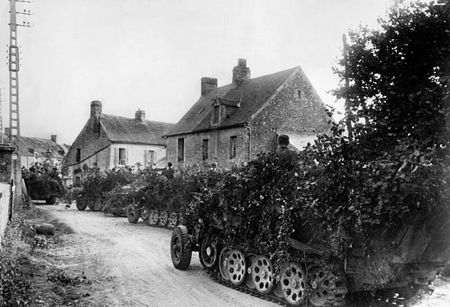 Attempting to avoid Allied warplanes that ruled the skies, heavily camouflaged German vehicles pass through a small French village in August 1944.