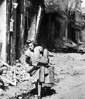 A woman runs through the streets with her last few possessions, perhaps heading to one of the city's bunkers, during an American daylight air raid on Hamburg, July 1943.