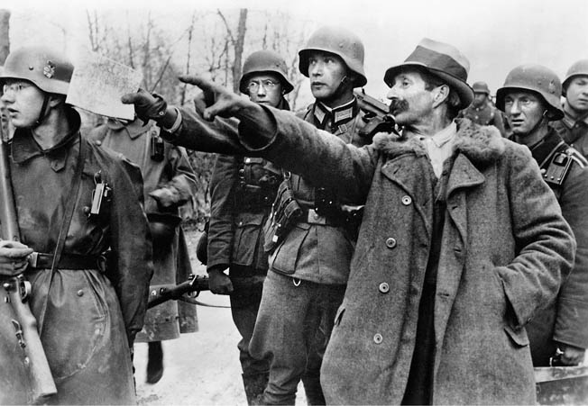 A Yugoslav civilian, perhaps under duress, points to positions he believes are occupied by units of the Yugoslav Army. His Nazi interrogators appear in a hurry to continue their advance.