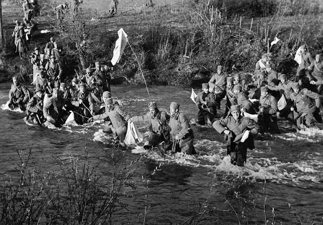 Wading across a small stream and prominently waving white flags, Yugoslav soldiers approach German troops and surrender, preferring captivity to the prospect of combat with an enemy that was already experienced in warfare and confident of victory. During their swift conquest of Yugoslavia, the Germans swept aside most of the organized resistance they encountered.