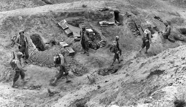 Soldiers of the U.S. 1st Infantry Division dig in near El Guettar, where they went into action against the German 10th Panzer Division and won. The 1st Division was a crack combat unit, molded under the leadership of Generals Allen and Roosevelt.