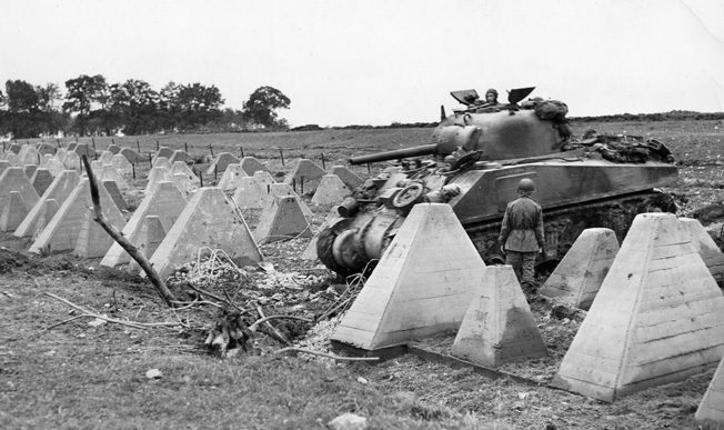 A Sherman tank plows through a gap in the Dragon's Teeth of the German Siegfried Line. Dragon's Teeth were no deterrent to Erickson and his tankmates.