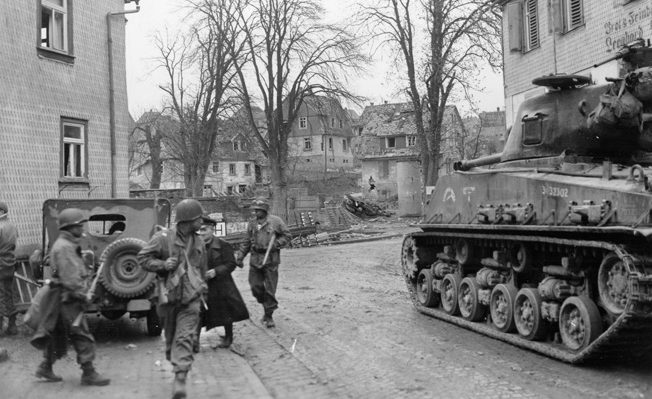 "A 12th Armored Division M4A3-E8 ""Easy 8"" tank supports African American infantry from the 66th Armored Infantry Regiment as they capture a German prisoner in the city of Erbach."