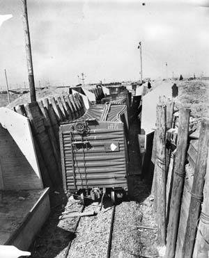 The crushed roofs and sides on steel railway cars on a revetted siding give stark visual evidence of the power of the blast that was heard and felt in San Francisco, 40 miles away.