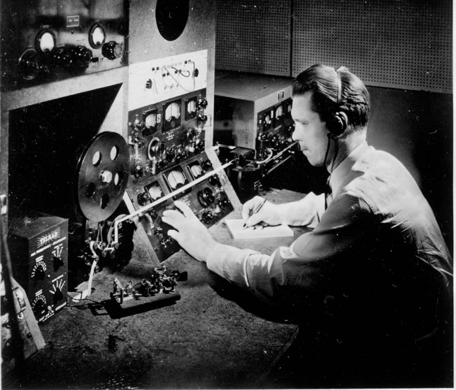 A technician mans a communications position, monitoring radio transmissions between distant points.