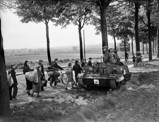 Belgian refugees flee the fighting as a British Universal Carrier prepares to head to the front, May 12,