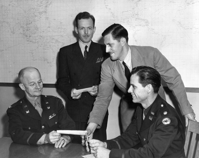 "Major John S. Detlie, far right, poses with Colonel Richard Park, Seattle District Engineer, and two civilians who received checks as part of an ""Ideas for Victory"" promotional campaign. Detlie, an art director and set designer for MGM Studios, was in charge of camouflaging Boeing's Seattle aircraft plant."
