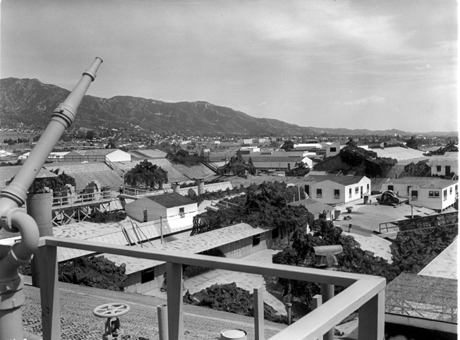 In this view of the Lockheed factory camouflage at Burbank, looking southeasterly toward Glendale, one gets an idea how complex much of the structure really was. On the left in the foreground is a hose nozzle for firefighting. Being made of wood, burlap, and tar, the whole affair was a potential fire hazard.