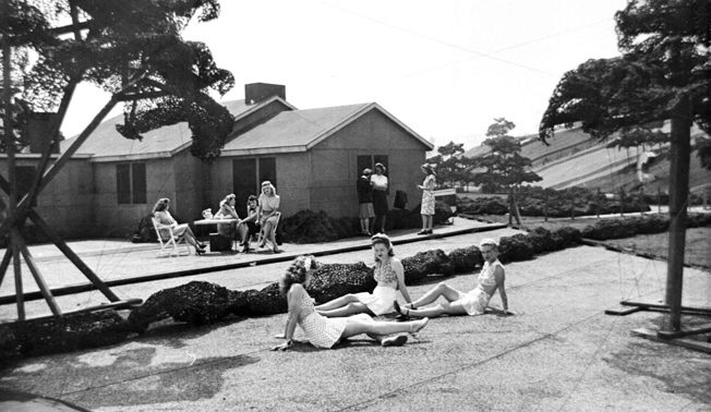 """A group of employees gathers on a """"lawn"""" in Boeing Wonderland. This was probably the only time these women were ever allowed to visit; a few months earlier it would have been a federal crime to be here, and a few months later the whole village was gone. In contrast to many other """"homes"""" in the """"subdivision,"""" the one shown here was close to accurate height."""