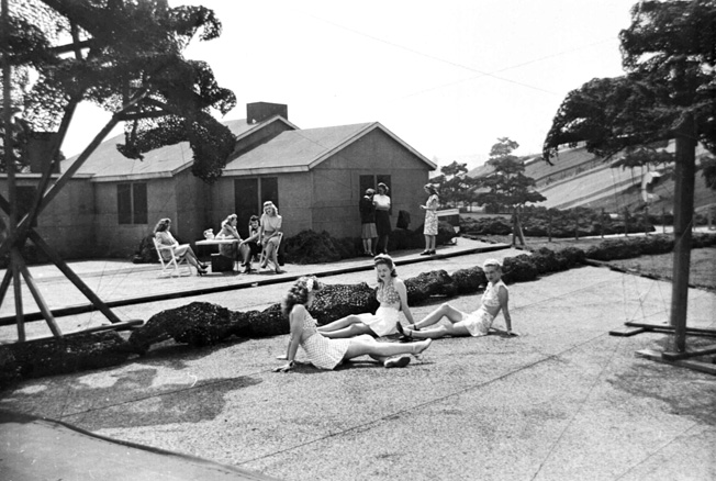 "A group of Boeing employees gathers on a ""lawn"" in Wonderland. This was probably the only time these women were ever allowed to visit; a few months earlier it would have been a federal crime to be here, and a few months later the whole village was gone. In contrast to many other ""homes"" in the ""subdivision,"" the one shown here was close to accurate height."