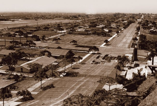 """This excellent overview of the camouflaged Douglas factory in Santa Monica shows how detailed and realistic the false rooftop neighborhoods were. In addition to tree-lined streets and buildings of varying shapes and sizes, there were sidewalks, detached garages, and empty lots. Note the sizable, but unplanned, """"potholes""""—actually rips in the cammo netting, in the center. By the time this picture was taken in 1945, such potholes were no longer being repaired. The Clover Field flightline is visible in the upper left."""