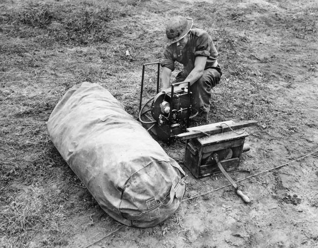 A British soldier prepares an Italian generator to inflate the fake tank body, which is still in its bag. The forge pump, in the wooden box, will be used to inflate the turret.