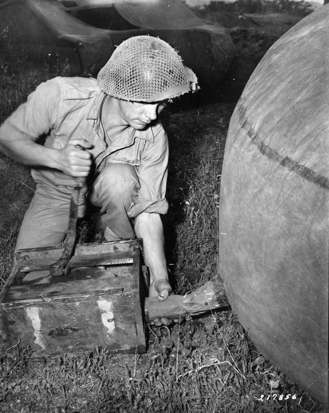 A soldier attaches the pump tube to one of the tank's valves.