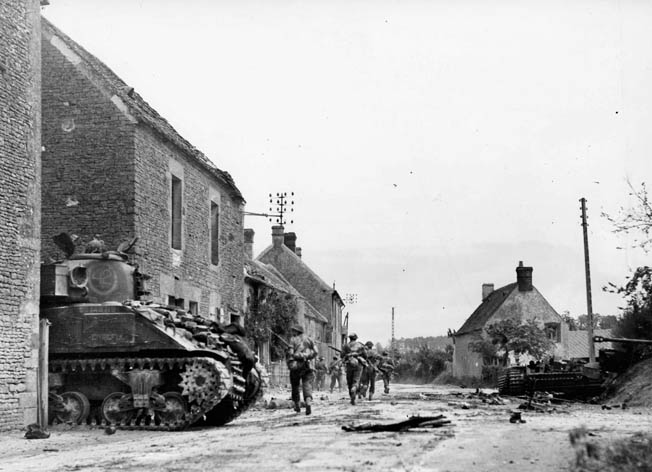 "Canadian troops, accompanied by a Sherman/Grizzly tank, depart St. Lambert-sur-Dives. The ""Corridor of Death"" is less than a mile up ahead."