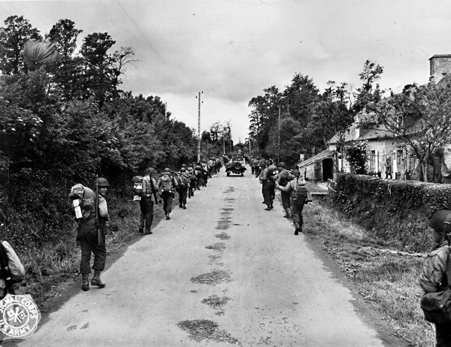 Smiling and looking confident, an unidentified American infantry unit advances through a village in Normandy.